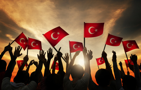 politics: Silhouettes of People Holding the Flag of Turkey Stock Photo