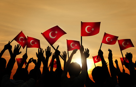 Silhouettes of People Holding the Flag of Turkey Imagens