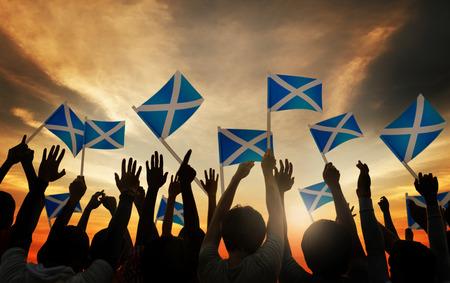 personas saludando: Grupo de personas que ondeaban banderas escocesas en Contraluz Foto de archivo