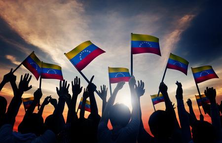 personas saludando: Grupo de personas que ondeaban banderas de Venezuela en Contraluz Foto de archivo