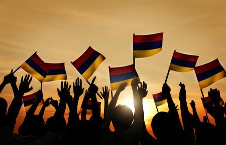 armenian woman: Group of People Waving Armenian Flags in Back Lit Stock Photo