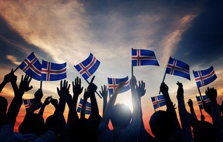 gente saludando: Grupo de personas que ondeaban banderas de Islandia en Contraluz Foto de archivo