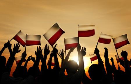 personas saludando: Grupo de personas que ondeaban banderas polacas en Contraluz