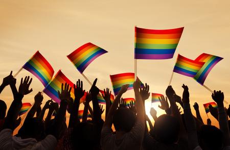 lesbianas: Siluetas de personas que tienen orgullo gay s�mbolo de la bandera Foto de archivo