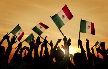bandera de mexico: Siluetas de personas que tienen la bandera de M�xico Foto de archivo