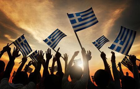 Silhouettes of People Holding Flag of Greece photo