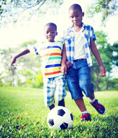 hermanos jugando: Ni�os africanos que juegan Ejercicio Concepto de F�tbol Foto de archivo