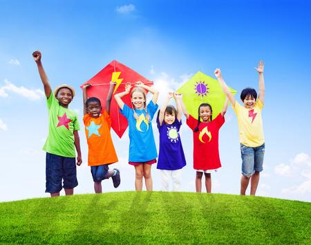 niños jugando en el parque: Grupo de niños que juegan al aire libre Cometas Foto de archivo