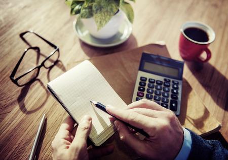 電卓を操作するビジネスマンの手 写真素材