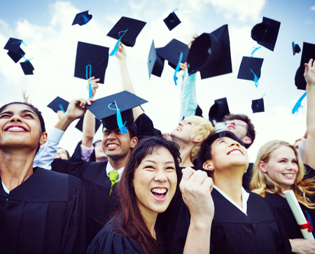 Casquillos de la graduación lanzados en el aire