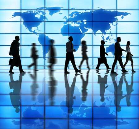 indoors: Side View Photo Of Silhouettes Of Business People Walking Indoors And Cartography Of The World Above. Stock Photo