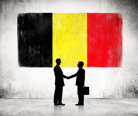 Two Businessmen Shaking Hands On A Background With National Flag Of Belgium photo