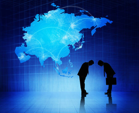 social grace: Two silhouettes of businessmen with blue cartography of Asia as a background.