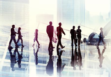 personas caminando: Siluetas de hombres de negocios que recorren el interior de la Oficina