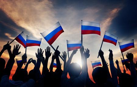 gente saludando: Grupo de personas que ondeaban banderas de Rusia en Contraluz