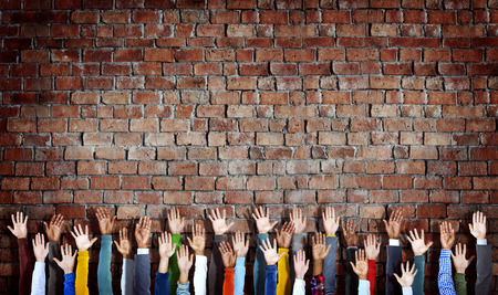 Group of Diverse Hands Raised on Brick Wall