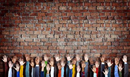manos levantadas: Grupo de Manos diversas Criado en la pared de ladrillo