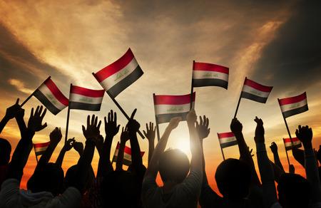 gente saludando: Siluetas de personas que ondeaban la bandera de Irak