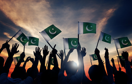 personas saludando: Grupo de personas que ondeaban la bandera de Pakist�n en Contraluz Foto de archivo