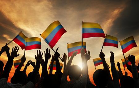 gente saludando: Grupo de personas que ondeaban banderas colombinas en Contraluz
