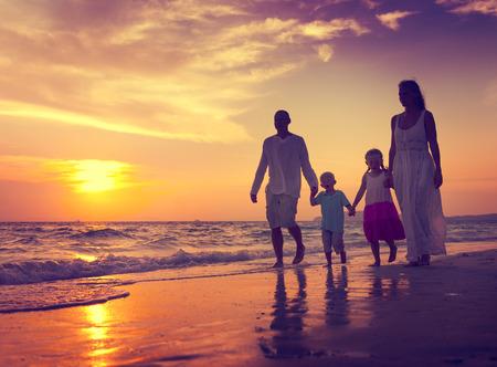 �sunset: Familia que recorre la playa de la puesta del sol Viaje de concepto de vacaciones