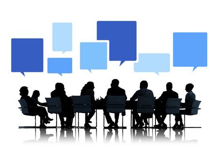 Sihouettes van mensen uit het bedrijfsleven in een vergadering met tekstballonnen