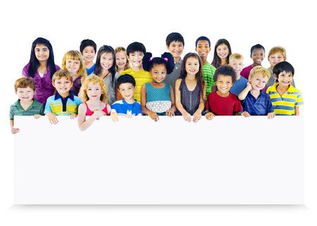 空のバナーを保持している子供たちの多民族グループ 写真素材