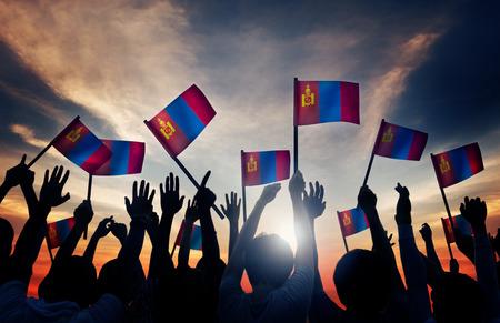 personas saludando: Grupo de personas que ondeaban banderas de Mongolia en Contraluz