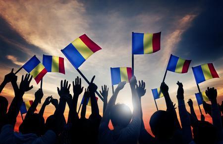 gente saludando: Grupo de personas que ondeaban banderas rumanas en Contraluz Foto de archivo