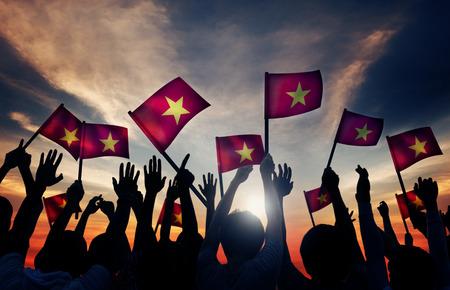 personas saludando: Grupo de personas que ondeaban banderas vietnamitas en Contraluz