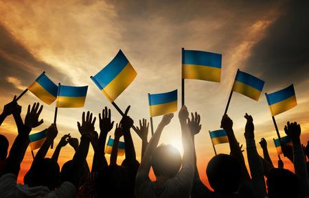 personas saludando: Grupo de personas que ondeaban banderas ucranianas en Contraluz Foto de archivo