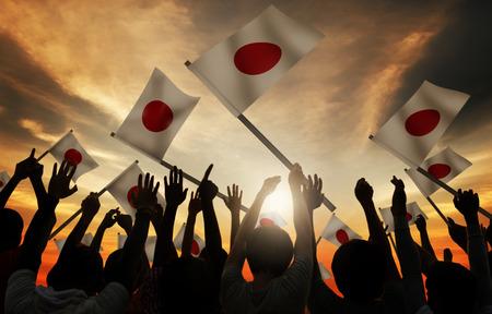 gente saludando: Grupo de personas que ondeaban banderas japonesas en Contraluz