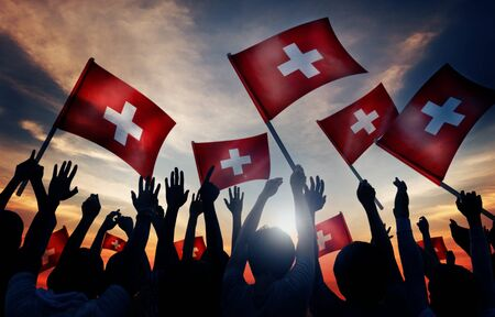 swiss culture: Silhouettes of People Holding Flag of Switzerland Stock Photo