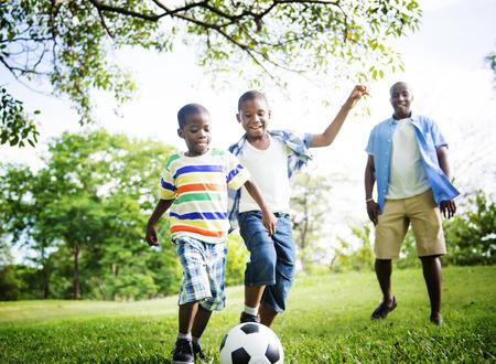 jugando futbol: Familia africana de vacaciones Felicidad Holiday Actividad Concept