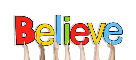 obedecer: Grupo de manos sosteniendo la carta Believe
