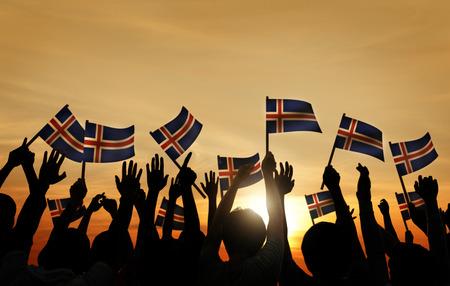 personas saludando: Grupo de personas que ondeaban banderas de Islandia en Contraluz Foto de archivo