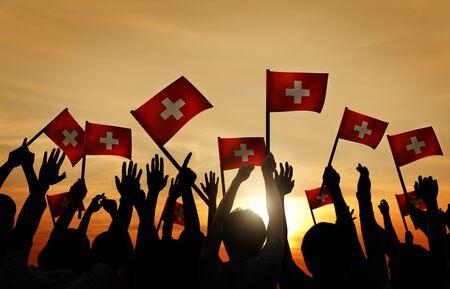 gente saludando: Grupo de personas que ondeaban banderas de Suiza en Contraluz