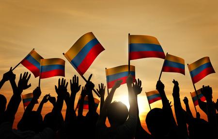 personas saludando: Grupo de personas que ondeaban banderas colombinas en Contraluz