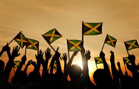gente saludando: Grupo de personas que ondeaban la bandera de Jamaica en Contraluz Foto de archivo