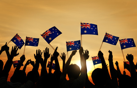 national flag: Group of People Waving Australian Flags in Back Lit Stock Photo