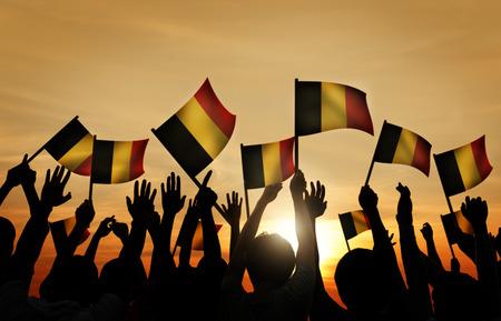 gente saludando: Grupo de personas que ondeaban banderas belgas en Contraluz