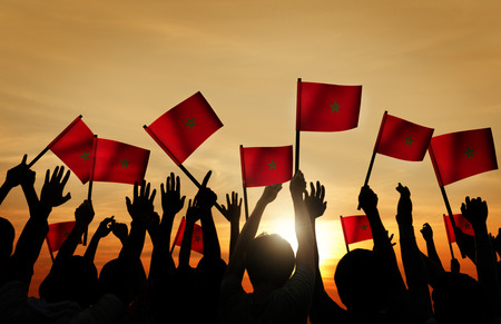 moroccan culture: Silhouettes of People Holding the Flag of Morocco