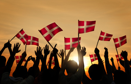 Silhouettes of People Holding the Flag of Denmark Zdjęcie Seryjne