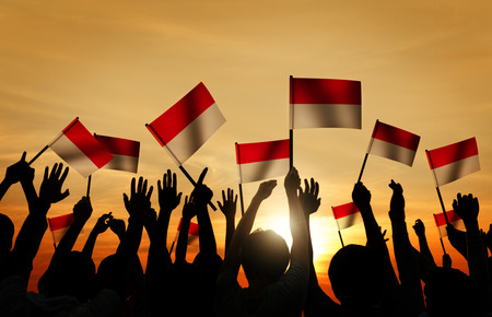 Silhouettes of People Holding the Flag of Indonesia Stock Photo