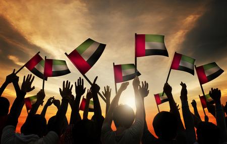 gente saludando: Grupo de personas que ondeaban la bandera de los Emiratos �rabes Unidos en Contraluz