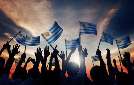 personas saludando: Grupo de personas que ondeaban banderas uruguayas en Contraluz