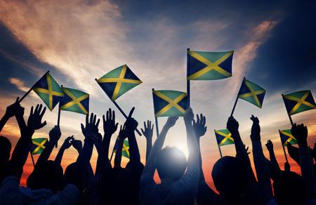 personas saludando: Grupo de personas que ondeaban la bandera de Jamaica en Contraluz Foto de archivo