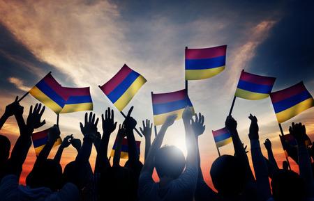 gente saludando: Grupo de personas que ondeaban banderas de Armenia en Contraluz Foto de archivo