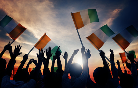 irish ethnicity: Silhouettes of People Holding Flag of Ireland