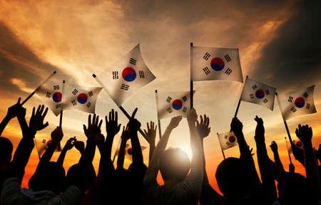gente saludando: Grupo de personas que ondeaban banderas de Corea del Sur en Contraluz